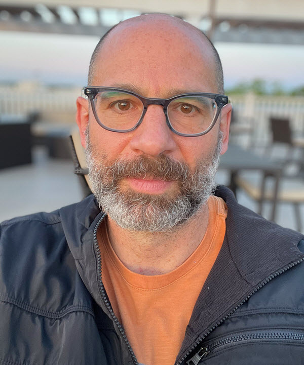 Close up photo of David Plotz, a white man with glasses, bald head, and salt and pepper beard, in an orange t-shirt and blue jacket
