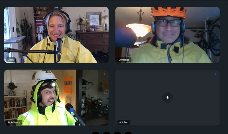 Screenshot from video meeting. There are 4 boxes with 3 people, all in bright yellow jackets with headphones.
