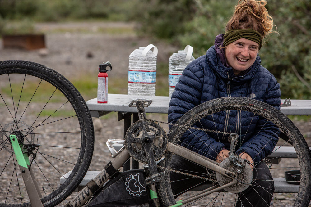 Kailey is sitting at a picnic table facing and fixing a muddy, upside bike. She has a blue puffy coat and a green hairband holds back her reddish hair. She is smiling.