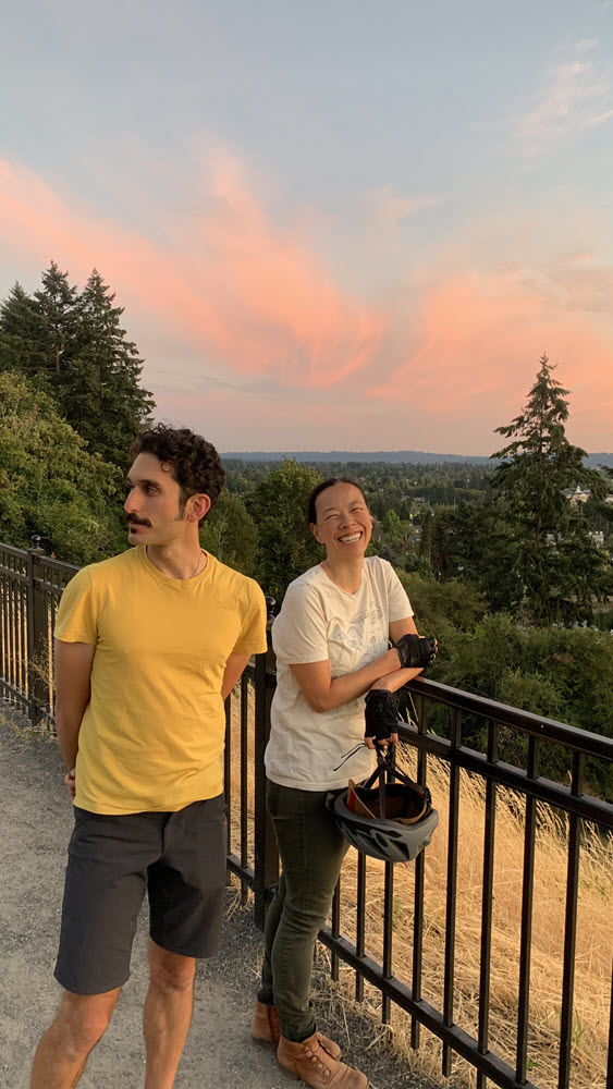Photo of two people standing along a black metal fence with a distant view of wispy clouds. She has a white shirt and dark pants and holds a bike helmet and smiles while looking at the camera. He has a mustache and yellow shirt and dark shorts and looks away.