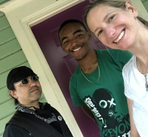 Photo is a selfie taken by a woman standing on the right. She has light skin and her hair is pulled back and she's smiling. Behind her are a young man with dark skin and a green shirt and another older man with a black hat and small glasses.