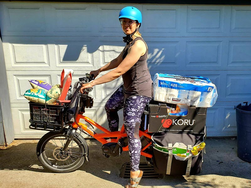 A side view of a woman posing on a bike. The bike is loaded up with packages on the front and back racks. She is smiling, looking, at the camera, and wearing a helmet.