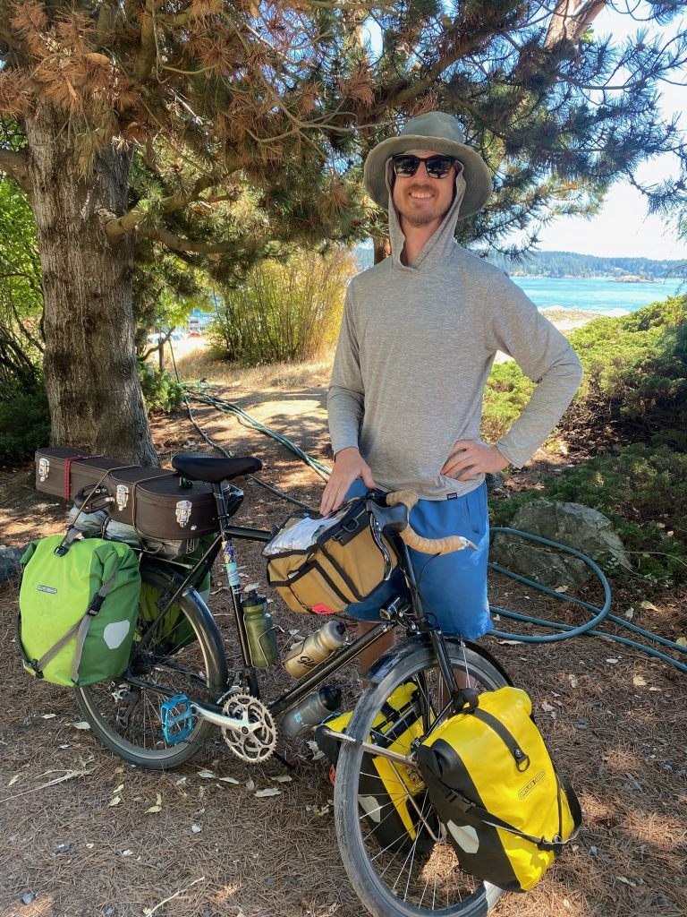Guthrie stands in the shade with a distant view of water behind. He wears a hoodie, hat, and sunglasses, and stands next to his bike, loaded up with stuffed panniers.