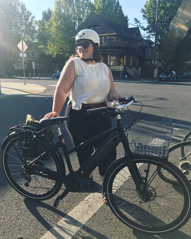 A woman stands in the middle of a road. She wears a white sleeveless top, white bike helmet, and black pants, and she holds a black bike, and looks off-camera.